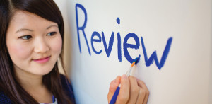 "Photo of girl painting the word ""review"" on a wall"