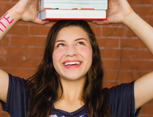 Photo of college-aged girl with text books