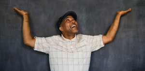 Photo of smiling man with his hands in the air