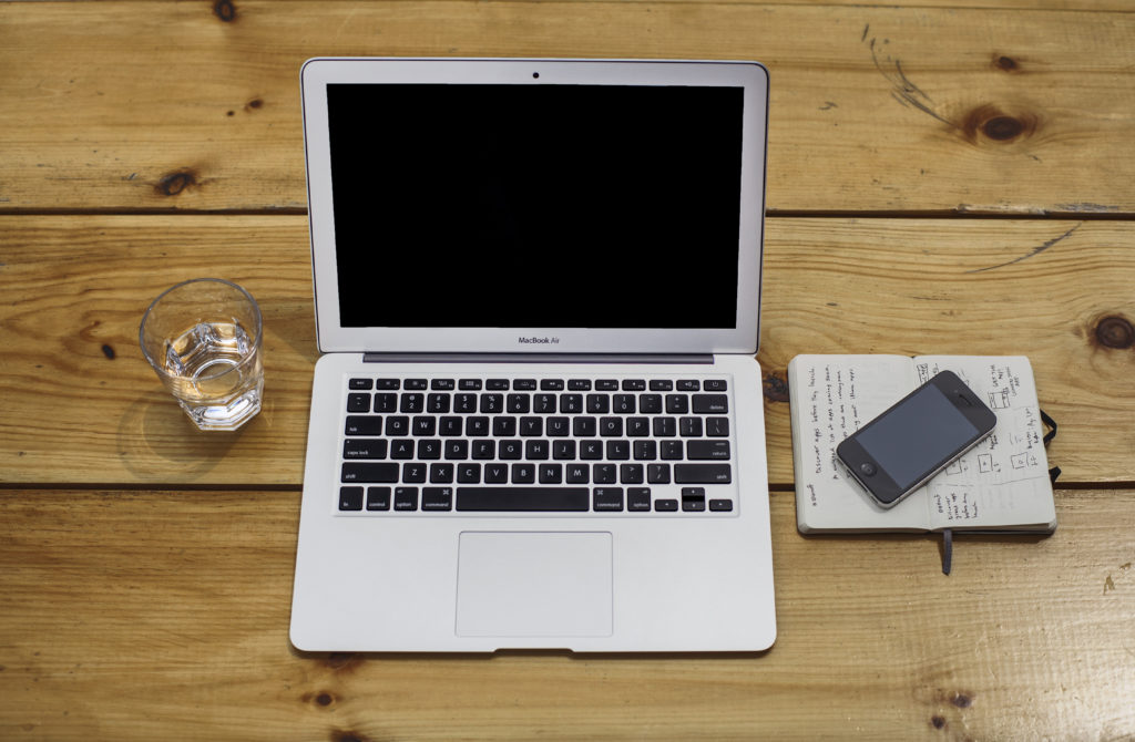 Photo of a laptop, smartphone and notebook on a table